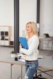 Vrouwelijke werknemer die een omslag in het bureau houden stock fotografie