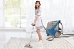 Vrouwelijke werknemer die vuil verwijderen uit tapijt met professionele stofzuiger, binnen stock fotografie