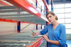 Vrouwelijke werknemer het schrijven inventaris en het denken in pakhuis Stock Foto