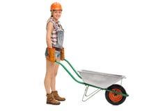 Vrouwelijke werknemer het stellen met lege kruiwagen Royalty-vrije Stock Fotografie