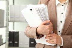 Vrouwelijke werknemer met documenten in archief stock foto's
