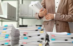 Vrouwelijke werknemer met documenten in archief stock foto
