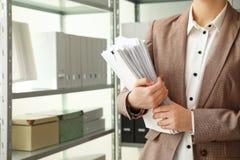 Vrouwelijke werknemer met documenten in archief, close-up royalty-vrije stock afbeelding