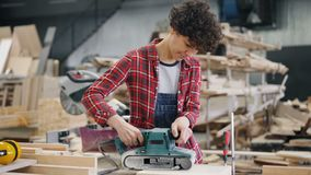 Vrouwelijke werknemer oppoetsend hout met riemschuurmachine die in houtworkshop werken stock footage