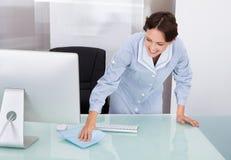 Vrouwelijke werknemer schoonmakend bureau stock afbeelding
