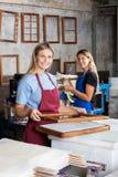 Vrouwelijke werknemers die Documenten samen in Fabriek maken Stock Foto's