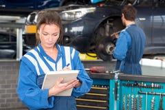 Vrouwelijke werktuigkundige tijdens een MOT-test stock afbeeldingen