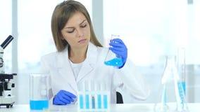 Vrouwelijke wetenschappelijk onderzoeker die blauwe oplossing in fles in laboratorium bekijken stock videobeelden