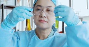 Vrouwelijke wetenschapper bewegende buis voor haar experiment stock video