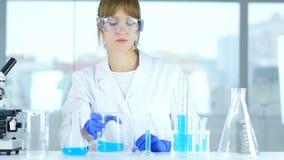 Vrouwelijke wetenschapper bezige het doen onderzoek en reactie in laboratorium stock video
