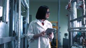Vrouwelijke wetenschapper die door laboratorium lopen stock video