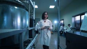 Vrouwelijke wetenschapper die door laboratorium lopen stock footage