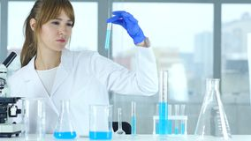 Vrouwelijke wetenschapper die in laboratorium, het gieten chemische oplossing in testton werken stock video