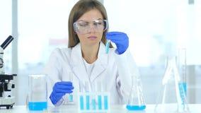 Vrouwelijke wetenschapper die in laboratorium, het gieten oplossing in reageerbuis werken stock videobeelden