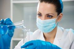 Vrouwelijke Wetenschapper die in Laboratorium werkt Stock Foto's
