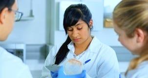 Vrouwelijke wetenschapper die op een blocnote 4k schrijven stock video