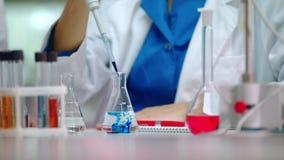 Vrouwelijke wetenschapper gietende reagens in laboratoriumfles Wetenschapper die chemische reactie doen stock video
