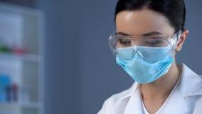 Vrouwelijke wetenschapper in masker en beschermende glazen op werkende plaats, de kosmetiek royalty-vrije stock afbeeldingen