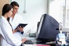 Vrouwelijke wetenschappers die een monitor met behulp van Royalty-vrije Stock Afbeelding
