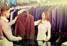 Vrouwelijke winkel hulp helpende klant om kostuum te kiezen royalty-vrije stock afbeelding