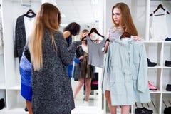 Vrouwelijke winkelmedewerker die twee punten van kleren aanbieden aan de klanten in manieropslag Stock Foto