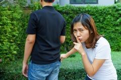 Vrouwelijke zakkenroller die een portefeuille van achter zak op jeans stelen Stock Foto