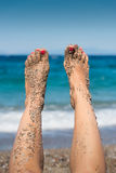 Vrouwelijke zandige voeten omhoog in de lucht Stock Foto's