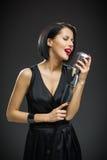 Vrouwelijke zanger met gesloten ogen die mic houden royalty-vrije stock afbeeldingen