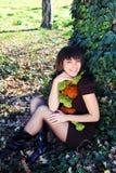Vrouwelijke zitting onder een boom Stock Afbeeldingen