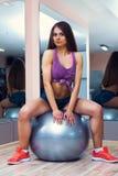 Vrouwelijke zitting op een gymnastiekbal Royalty-vrije Stock Foto's