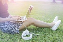 Vrouwelijke zitting op hebzuchtgras door toetsenbord van te ontspannen en te typen Royalty-vrije Stock Afbeelding