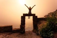 Vrouwelijke zitting op oude zandsteendeuropening met mistige zonsopgang royalty-vrije stock afbeeldingen