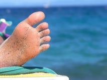 Vrouwelijke zool die van voet, op strandlaag ontspannen, blauwe waterbackgro Stock Afbeelding