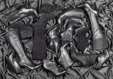 Vrouwelijke zwarte schoenen en laarzen op zwart satijn Stock Foto's