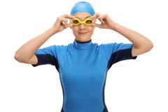 Vrouwelijke zwemmer die haar zwemmende beschermende brillen aanpassen Stock Foto