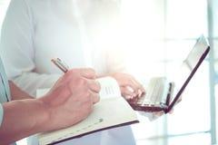 Vrouwen arts die met laptop computer en mannen artsen het schrijven notitieboekje over het geduldige profiel van ` bespreken s Royalty-vrije Stock Foto
