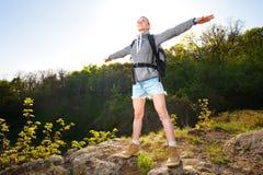 Vrouwen backpacker bevindende open hand die van de mening in bos genieten Stock Fotografie