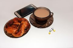 Vrouwen bedrijfskoffiepauzeconcept met mobiele telefoon, kop van hete drank, broodje en oorringen stock fotografie