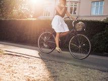 Vrouwen berijdende fiets langs de straat Royalty-vrije Stock Foto