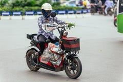 Vrouwen berijdende motorfiets met haar bezittingen op de weg in Hanoi, Vietnam royalty-vrije stock foto's