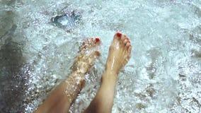 Vrouwen bespattende voeten in de pool Dolly schot van een jonge vrouw die gelukkig haar voeten in de pool spuiten stock footage