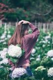 Vrouwen bevindende Draai rond aan de bloemen van de tuinhydrangea hortensia royalty-vrije stock afbeelding