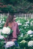 Vrouwen bevindende Draai rond aan de bloemen van de tuinhydrangea hortensia stock fotografie