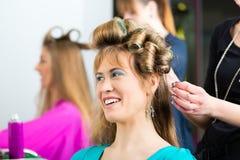 Vrouwen bij de kapper met krullen stock foto's