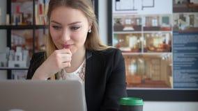 Vrouwen binnenlandse ontwerper het drinken koffie en het werken aan laptop computer in bureau stock videobeelden