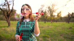 Vrouwen blazende zeepbels in openlucht - langzame motie stock footage