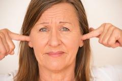 Vrouwen blokkerende oren met vinger royalty-vrije stock fotografie