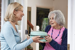 Vrouwen Brengende Maaltijd voor Bejaarde Buur stock foto's