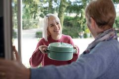Vrouwen Brengende Maaltijd voor Bejaarde Buur royalty-vrije stock afbeelding