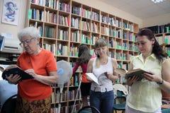 Vrouwen in de boeken van een openbare bibliotheeklezing Royalty-vrije Stock Afbeeldingen